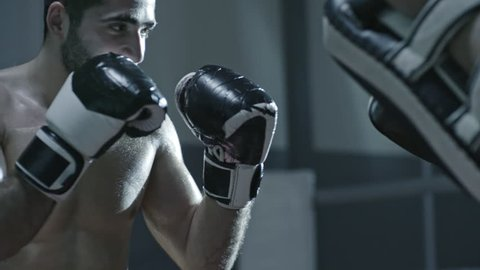 Medium shot of shirtless MMA fighter in boxing gloves hitting and leg kicking punching pads held by his sparring partner