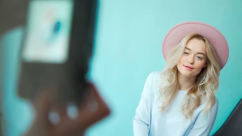 Behind the scene: model girls are posing for a photographer in gentle dresses and pink hat. Backstage: photographer takes pictures of the model in dresses. The process of work of professional model