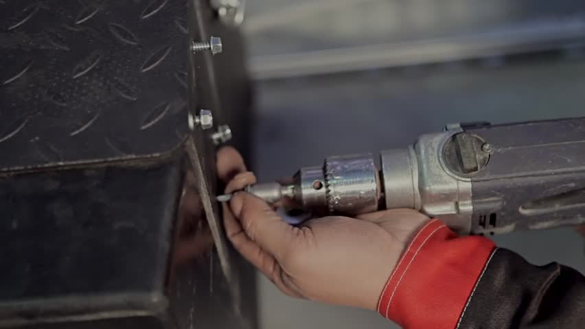 Man using an electric hand drill. / Man using an electric hand drill to drive a self drilling screw into a a piece of primed metal. Close up. Screwdriver