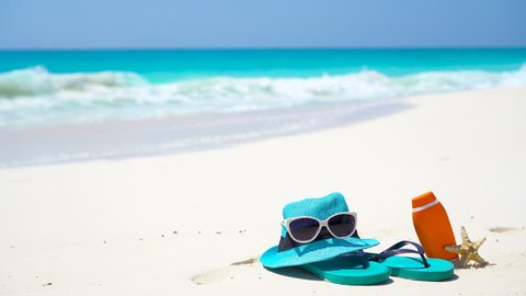 Beach accessories - straw hat, flip flops, bottle of cream and sunglasses on the beach
