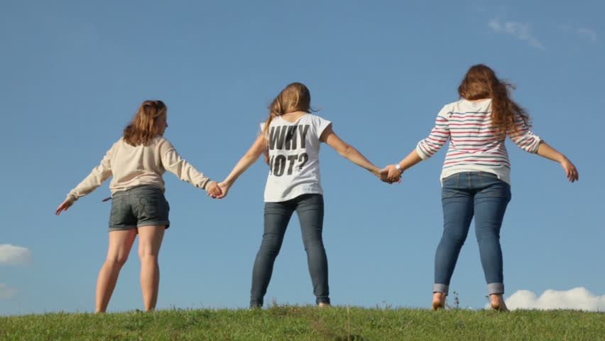 Three young girls hold hands and raise them on grass hill, view from behind at sunny summer day
