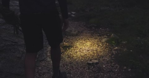 man walking in forest by night with headlamp light. Group of friends summer adventure journey in mountain nature outdoors. Travel exploring Alps, Dolomites, Italy. 4k slow motion 60p video