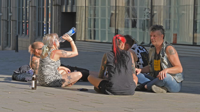 LUBECK, GERMANY - MAY 28: Punk girl drinking water with friends on pedestrianized street on May 28, 2017 in Lubeck, Germany.