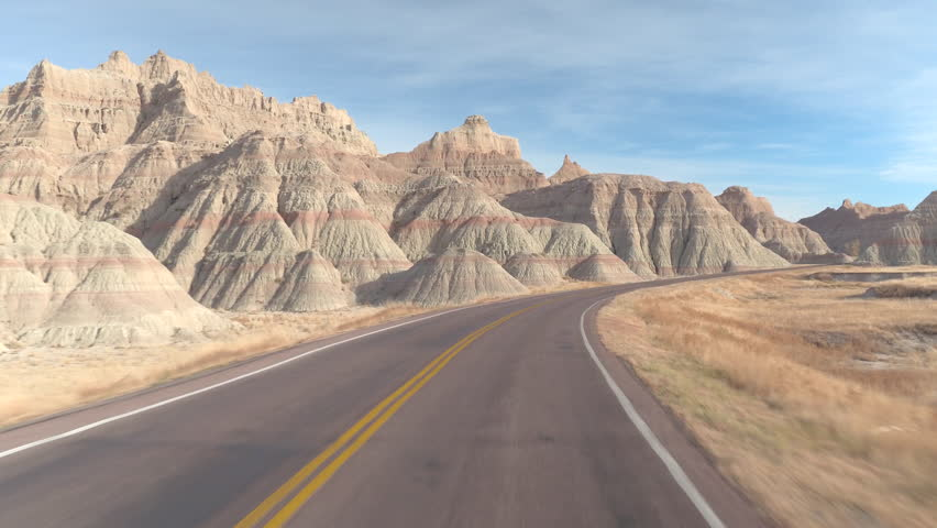 FPV: Driving along the empty road winding past amazing Badlands landscape with rocky sandstone mountains. Traveling across the Badlands grassland desert in South Dakota. Road trip across United States | Shutterstock HD Video #27680824