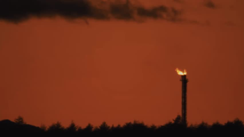 Burning industrial pipe silhouette at shale gas producing mine in forest under setting sun light