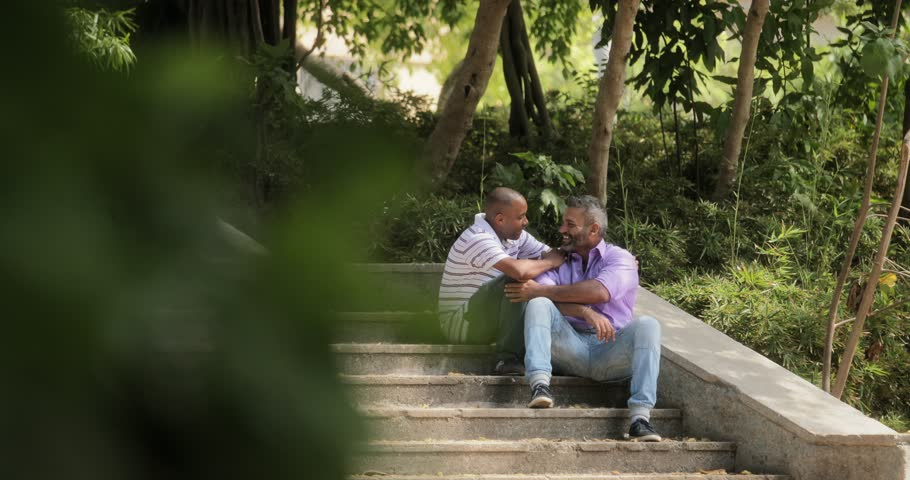Homosexual couple, gay people, same sex marriage between hispanic men, multi-ethnic lgbt relationship. Kiss between partners, male friends showing love and affection in city park