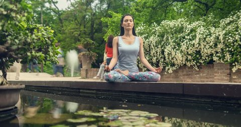 Young woman sits in yoga pose. Time lapse. Cinemagraph. Seamless Loop