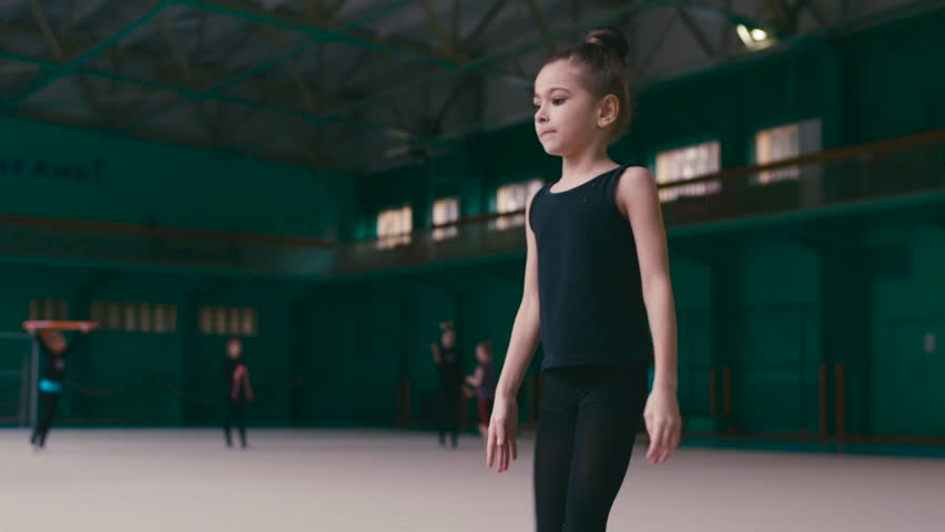 Adorable little girl diligently stretches before the training in a gym. Practicing sport, sport uniform, twisted hair. Hobby, healthy lifestyle. Active lifestyle, being happy.