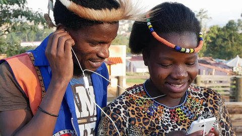 A black South African traditional woman standing alone listening to music on her cell phone telephone - in slow motion.