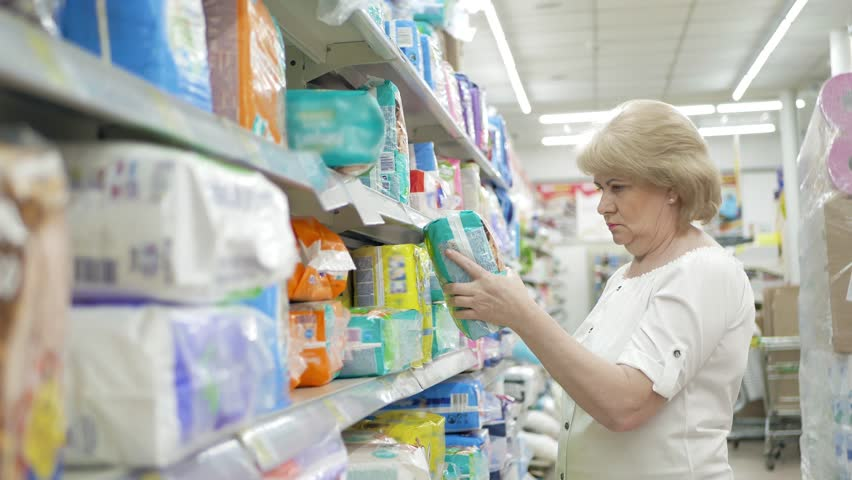 Elderly woman chooses baby diapers in the supermarket. Shopping in the store. Senior female carefully analyzing products