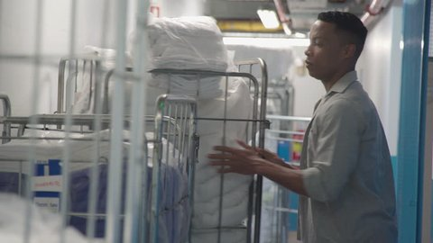 Worker organizing bundles of towels in laundry room