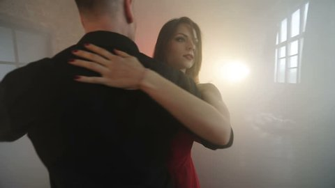 Tango professionals. A young man in black circles a beautiful woman in a red dress. Smoke in the studio. Steadicam shot. Slow motion.