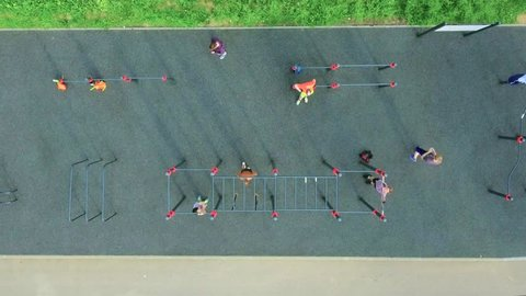 People train on an outdoor sports field in summer, aerial shot. Top view. Sports people of athletic build are pulled up, squeezed out, do various exercises on crossbeam and simulators outside