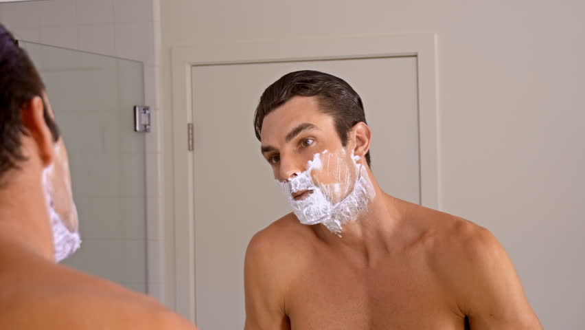 Athletic man shaving in the morning.