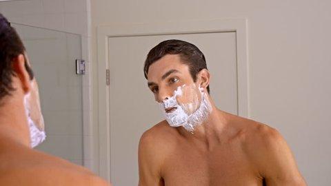 Athletic man shaving in the morning.