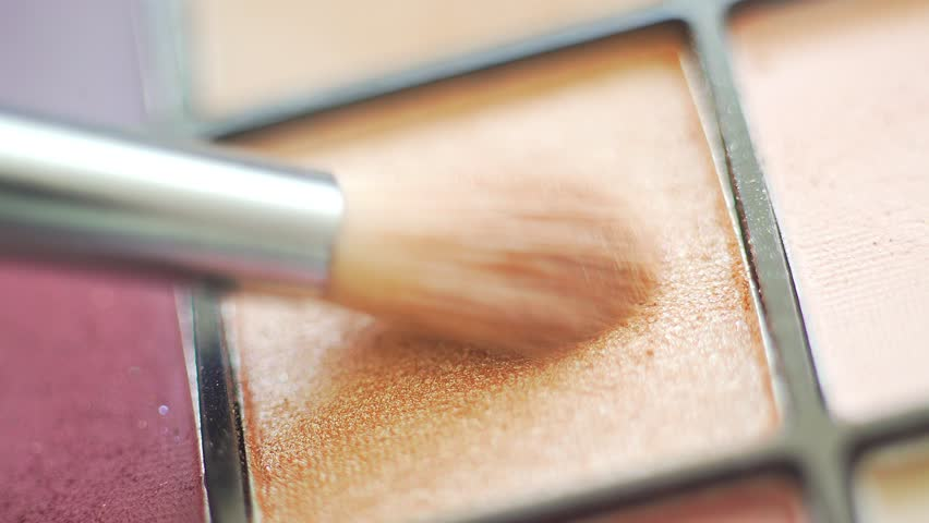 A palette with eye shadows and a makeup brush: women's cosmetics. Morning make-up. Decorative cosmetics: a palette with eye shadows, a brush.Evening make-up.Details of the make-up artist's work.