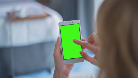 Young Woman in white top sitting on couch uses SmartPhone with pre-keyed green screen. Few types of gestures - scrolling up and down, tapping, zoom in and out.  10bit ProRes 444