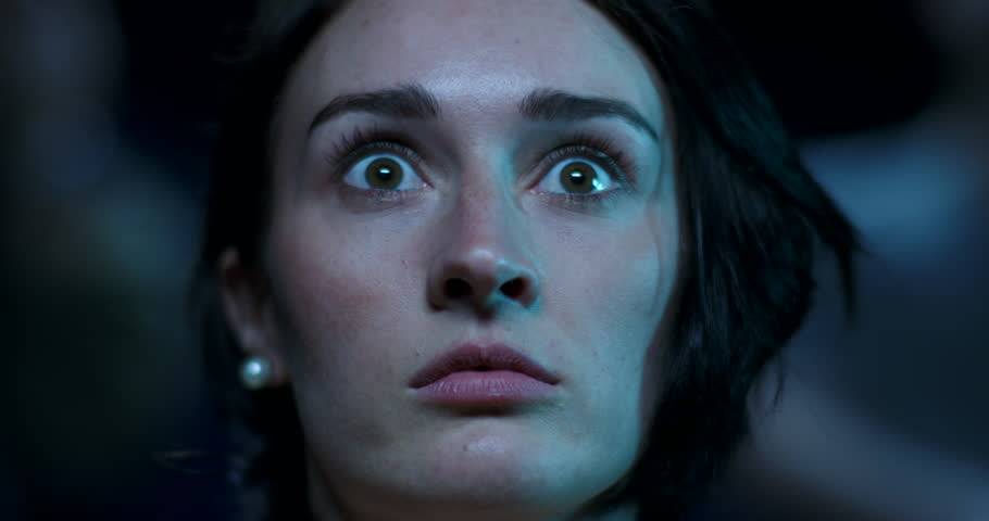 Close up of a scared young woman who jumps with fear while watching a scary movie at the cinema