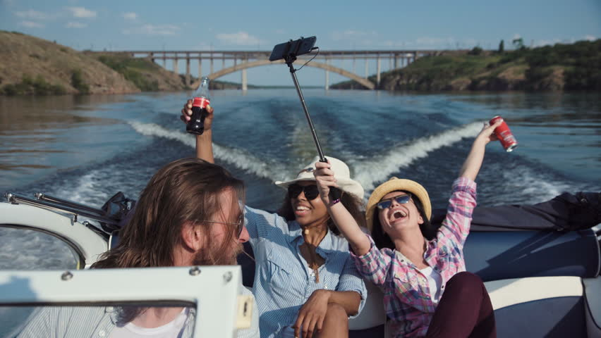 Laughing diverse family or three friends wearing sunglasses riding in a speedboat on a lake or river as they celebrate their summer vacation viewed close up