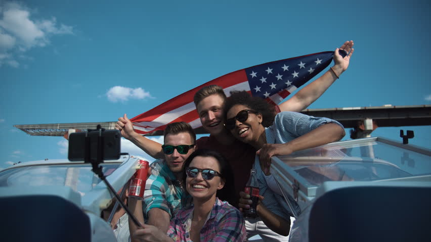 Group of diverse cheering laughing friends on a speedboat waving a patriotic American flag as they pass under a bridge in a low angle view looking up.