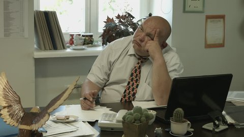 Ungraded: A bored fat bald office worker reluctantly pays attention to the visitor outside the frame, turns and looks straight to the camera. (av37113u)