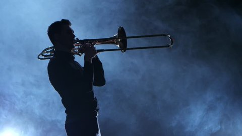 Silhouette professional musician man playing on trumpet. Smoky isolated studio