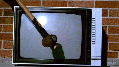 Sledge hammer smashing TV in slow motion