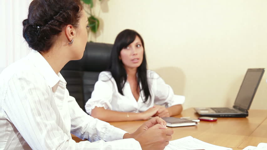 Two businesswomen discussing with colleague/client/customer in the office | Shutterstock HD Video #2788864