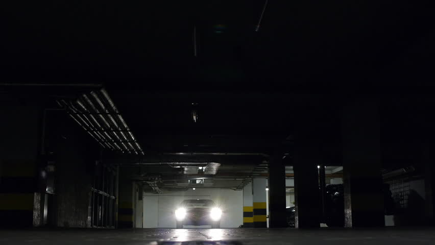 Classic car starting the engine and turning the lights on driving over camera in an underground car park  | Shutterstock HD Video #2789209