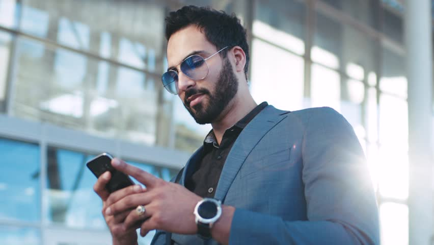 Rotation view of a bearded successful man using his phone by the airport entrance, sliding the screen, looking around. Stylish black suit, luxurious watch and sunglasses. Successful lifestyle.