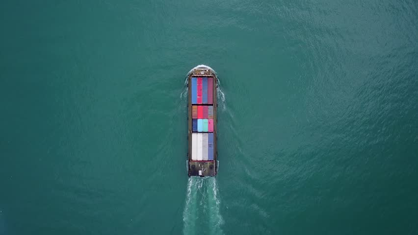 Small container ship sail away, vertical aerial shot, camera look straight down to beautiful dark turquoise coloured water. Vessel of small feeder class loaded with standard steel containers