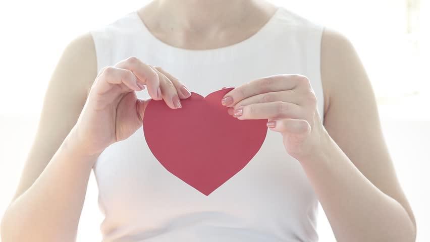 A girl breaks a paper heart