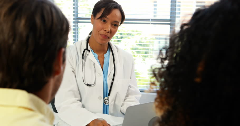 Smiling couple talking to doctor in clinic | Shutterstock HD Video #27938164
