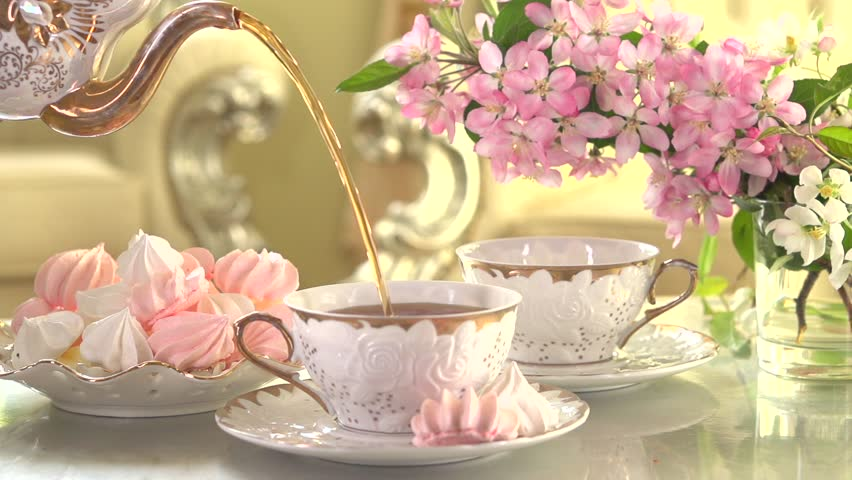 Tea Pouring. Porcelain cup of Healthy Tea closeup. Antique porcelain, luxurious interior. Slow motion video footage 240fps