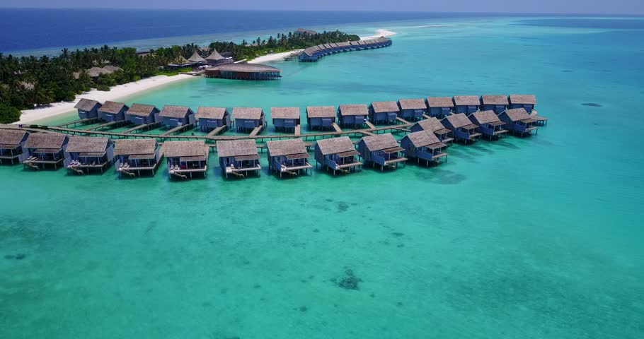 v03544 Aerial flying drone view of Maldives white sandy beach on sunny tropical paradise island with aqua blue sky sea water ocean 4k luxury 5 star resort hotel water bungalow hut relaxing holiday