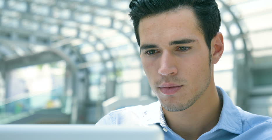 Young handsome businessman (student) in a blue shirt, at the table working with a laptop, serious, smiling. Concept: new business, business relationships, career growth, success, work online, station. | Shutterstock HD Video #27992464
