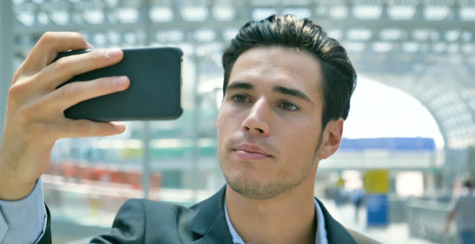 Portrait of a young handsome businessman (student) in a suit, smiling, video call on the phone, at the station, at the airport. Concept: new business, travel the world, communication, contacts, selfie