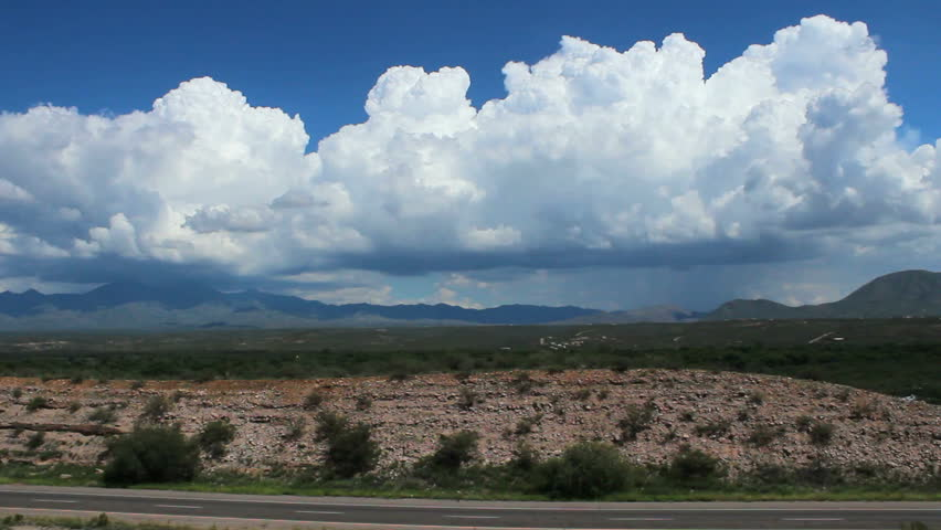 Time Lapse, Cars, trucks zip along American highway as thick, cloud mass swirls around mountains, creates beautiful, scenic background. 1080p | Shutterstock HD Video #2802064