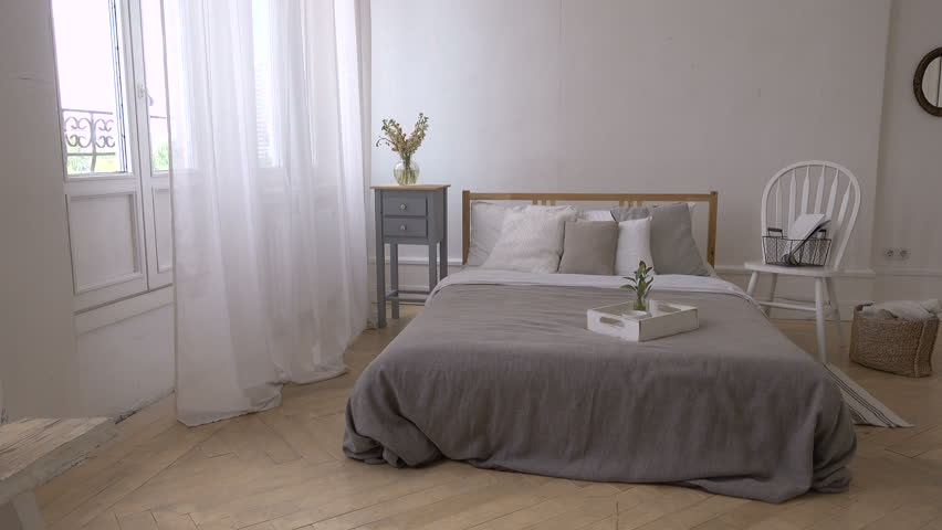 Interior of white and gray cozy bedroom with chair, basket, flowers, bedside table and mirror