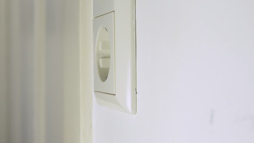 Hand Putting A Black Plug Into Wall Socket And Pulling It Out Again