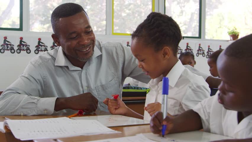 Teacher helps elementary school kids at their desk in class