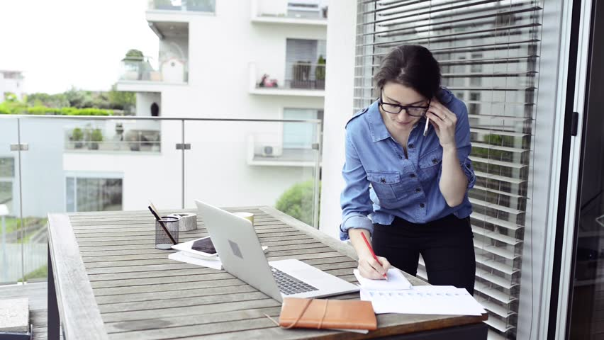 Woman on balcony working from home, making phone call. | Shutterstock HD Video #28056814