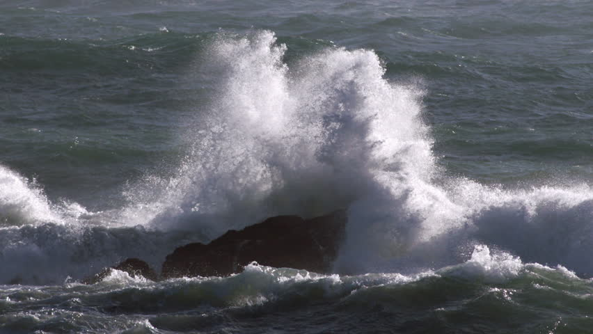 Huge ocean wave crashing onto rocks with lots of spray in super slow-motion - close-up