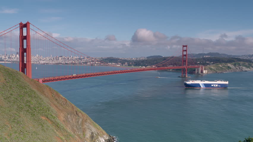 SAN FRANCISCO, CA - circa 2016: Big cargo ship carry automobile cars goes under the Golden Gate Bridge on sunny day. 4K