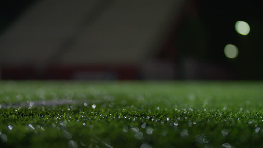 Macro of grass turf on a football field at night