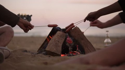 Group of young friends sitting by the fire on the beach, grilling sausages and playing guitar. Slowmotion shot
