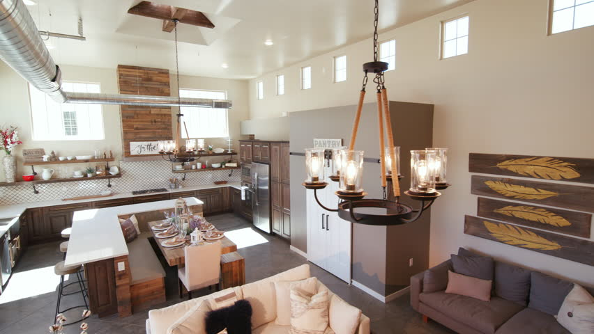 Modern Open Living Space with Kitchen Lower Left Angle. a lowering shot of a unique modern rustic industrial living open floor plan living space with kitchen and high ceilings  | Shutterstock HD Video #28083511