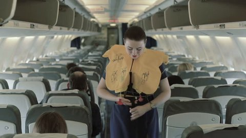 Young stewardess shows the manipulations with the life vest
