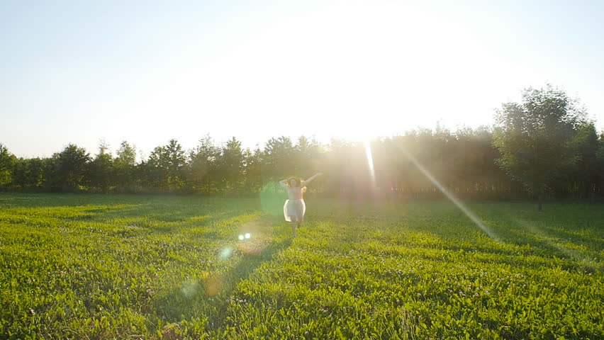 A young woman runs along a green glade at sunset #28109704