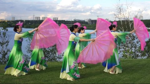 group of five asian women actresses in traditional chinese costumes with fans dancing at the riverbank outdoor